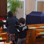 礼拝堂前方にこどもたち用の椅子を運んでいるのは神戸から曾おじいちゃまの寿先生による祝福をたのしみにやって来た姉弟。