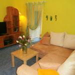 Wohnbereich mit Ecksofa, Tisch, TV-Schrank