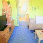 Wohnbereich mit Ecksofa, Tisch, TV-Schrank und Durchgang zum Schlafbereich und zum Badezimmer