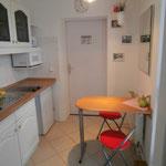 kleine Küche mit Spüle, Ceranplatten, Kühlschrank, Mikrowelle, Toaster,  Kaffeemaschine,  kleiner Esstisch