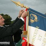 Le ministre Gérard Longuet épingle la Croix de la valeur militaire au drapeau.