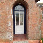 Die Tür hat ein Rundbogen- Oberlicht mit aufgesetzten Sprossen und blauem Blendrahmen, eingepasst in vorhandenes Mauerwerk