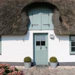Holzhaustür im Friesenstil mit aufgesetzter Füllung und einem historischem Türklopfer, das aufgesetzte Querprofil in der Mitte täuscht eine Teilung vor