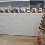 ⑮カウンター側、白い布スペースの上には板木彫り絵作品<旧作>の複製画額を並べて展示。