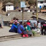 Peruanische Frauen die neben dem Markt ihre erstandenen Waren weiter verkaufen