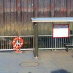 """7.  _Hello Elbe_ Selbstportrait. Vorbei an dem Schiffsanleger """"Dockland / Fischereihafen"""" mit dem imposanten Bürogebäude """"Dockland"""" aus Glas und Stahl, das wie ein Schiffsbug hinaus über das Wasser ragt."""