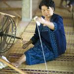 """「糸つむぎ」糸車を手で回しながら、綿のかたまりから引き出される糸に""""撚り""""をかけて紡ぎます。"""