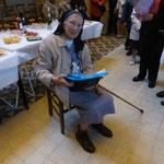 Soeur Marie pendant la remise des cadeaux ; derrière elle, le buffet attend les gourmands
