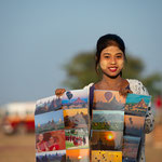 Young woman sells souvenirs to tourist doing a balloon ride, Myanmar © Stephan Stamm