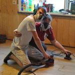 Nachdem der PVC raus ist, schleifen wir den darunter zum Vorschein gekommenen Fußboden.