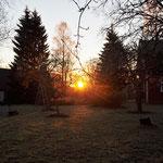 Hinter der Scheune geht die Sonne auf.