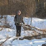 Erik rackt alte Baumkronenreste aus dem vorderen Garten.