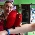 Zwei Papageien auf Katharinas Arm, Christine im Hintergrund