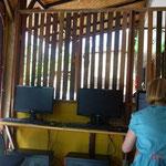"""Ein """"Holzgatter"""" vor einer Garage in welcher ein Näherei ist, dient als Internetcafé"""