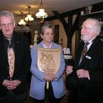 Dr. Telse Lubitz nimmt die Schnitzerei von Heinrich Schulz entgegen, damit sie in dem Heider Museum verwahrt und ausgestellt werden kann.