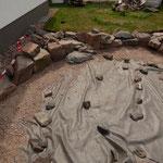 Die Blöcke und Steine werden in ein ca. 20cm starkes Schotterbett gesetzt.
