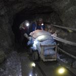 Zwei Bergleute plagen sich in einem ungesicherten Stollen mit einem Grubenhunt. Was sie aus dem erschöpften Bergwerk noch rausholen, gehört ihnen. Es braucht aber inzwischen 12-Stunden-Schichten, um sich von der Arbeit im Berg noch ernähren zu können.