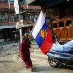 ネパールの旗を持って僧房に戻る若いお坊さん。お疲れさま~。