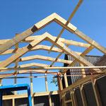 Damit die Dachsparrensets auch im Giebel im gleichen Abstand zueinander stehen wie unten auf den Wänden, wird oben eine Latte im entsprechenden Abstand provisorisch an den Sparren befestigt. Das verhindert, dass die Sparren sich verschieben