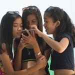 Foto des Monats Juni 2019 - Philippinas am Strand vor dem Handy,  Foto: Dr. Martin Hannemann, Nikon D800 /Nikkor 70-200/ 2.8,  Blende 2.8/ 1/640/ ISO 100