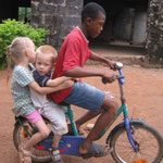 Emily and Elijah riding a bike in the village