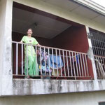 Hannah is standing on the balcony outside the upstairs parlor