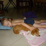 puppy sleeping with Naomi on the tile floor