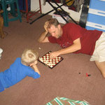 Dad is teaching Elijah how to play chess. Elijah is a fast learner.