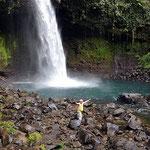 wie klein die Person gegenüber dem Wasserfall wirkt