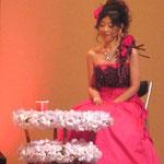 小島先生の解説の時に、ステージ横で座っています。お花の優しさがドレスの色にもあいました。