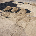 Die Waben der Platten werden mit Sand gefüllt.