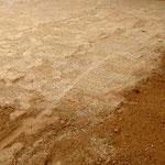 Abschließendes Abböschen des Zwischenraums zwischen Platten und Gras mit Sand.