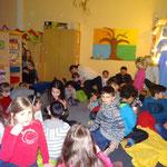 35 Kinder und ihre Eltern warten gespannt auf das, was sie erwarten wird.