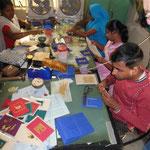 Eine Gruppe junger Behinderter stellt mit Reisstroh hübsche Karten her. Es bedeutet für sie Beschäftigung, Gemeinschaft und Verdienst.