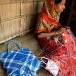 Die junge Frau der Agglomeration von Mymensingh-Stadt knüpft vor ihrer Hütte mit Plastikschnüren Taschen für den lokalen Markt. Sie ist stolze Unternehmerin dank dem Kleinkredit der Brüder.