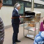 Direktor Blaum backt in einem Steinbackofen auf dem Schulhof Fladenbrot und Brötchen