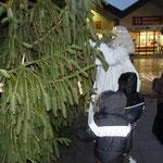 Gemeinsam mit einigen Kindern hängt der Engel Kugel an den Weihnachtsbaum