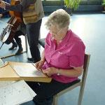 Frau Baumann spielt auf ihrer Tischharfe