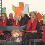 Kirchenbesucher beteiligen sich mit farbigen Liederblättern an der Predigt von Max v. Egidy über Glaube, Liebe und Hoffnung