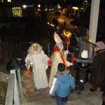 Unter Mithilfe des Engels verteilt der Nikolaus Geschenke an die Kinder