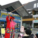 Der Clown hat an seiner Angel Süßigkeiten hängen die die Kinder mit den Mund schnappen sollen