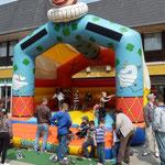 Kinder erfreuen sich an der großen Hüpfburg