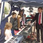 Ein Mädchen spielt unter Anleitung von Herrn Kurenkow ein Solo-Instrumentalstück