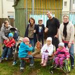 Einige Eltern und Kinder mit Frau Fischer an der alte maroden Feder-Wippe