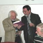 Herr Kitz überreicht Herrn Kindermann als Geschenk ein Buch