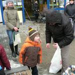 Der Kleine versucht mit dem Mund die Süßigkeiten von der Angel zu erhaschen