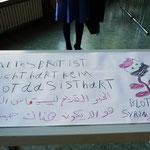 """Die Zeichnung eines syrischen Flüchtlings in deutscher und syrischer Sprache: """"Altes Brot ist nicht hart. Kein Brot zu haben, das ist hart"""". Rechts daneben ist ein Mensch zu sehen der gefoltert wurde in einer Blutlache auf dem Boden"""