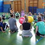 Kinder sitzen im Kreis gegenüber, nehmen Kontakt auf und spielen sich den Ball zu