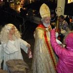 Der Nikolaus verteilt an die Kinder kleine Geschenke. Dabei hilft ihm sein Engel