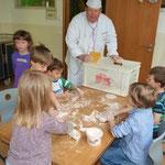 Eine andere Gruppe mformt unter Anleitung des Bäckers Brötchen mit verschiedenen Mehlsorten